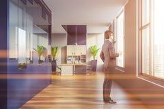 Homme dans l'intérieur bleu et gris de bureau de l'espace ouvert photos stock