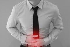 Homme dans l'uniforme de bureau ayant un mal de ventre/des problèmes intoxication alimentaire/estomac image libre de droits