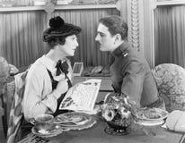 Homme dans l'uniforme et une femme s'asseyant ensemble à une table et regardant l'un l'autre (toutes les personnes représentées n Photographie stock