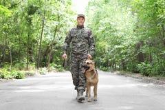 Homme dans l'uniforme militaire avec le chien, dehors images libres de droits