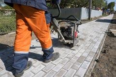 Homme dans l'uniforme orange utilisant la machine vibratoire de pavé pour la finition sur un site de construction de routes de tr images stock
