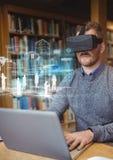 Homme dans la bibliothèque sur l'ordinateur portable utilisant le casque de réalité virtuelle de VR avec l'interface images stock