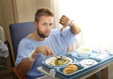 Homme dans la chambre d'hôpital mangeant de la nourriture de clinique d'alimentation saine dans l'expression déprimée de visage d photos libres de droits