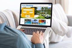 Homme dans la chambre tenant l'ordinateur portable avec l'hôtel en ligne de réservation de recherche photos libres de droits