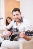 Homme dans la chemise blanche jouant la guitare et le chant Image libre de droits