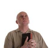 Homme dans la chemise de Brown avec la prière de bible Image libre de droits