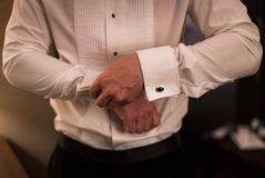 Homme dans la chemise habillée faisant vers le haut des boutons de manchette photographie stock libre de droits