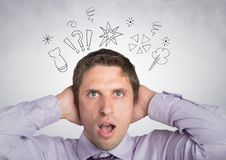 Homme dans la chemise lavendar avec des mains sur la tête avec des griffonnages contre le mur blanc Image libre de droits