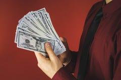 homme dans la chemise rouge avec une exploitation un paquet de factures dans sa main sur un fond rouge photos stock