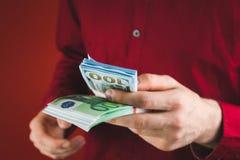 homme dans la chemise rouge tenant des paquets d'argent sur le fond rouge photos libres de droits