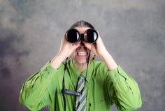 Homme dans la chemise verte et la cravate regardant par des jumelles Images libres de droits