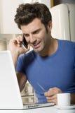 Homme dans la cuisine avec l'ordinateur portatif Images libres de droits