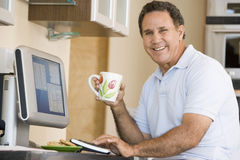 Homme dans la cuisine avec le sourire d'ordinateur et de café Image stock
