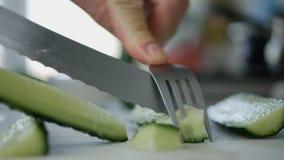 Homme dans la cuisine coupant un concombre dans les tranches pour une salade fraîche photos libres de droits