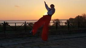 Homme dans la danse ukrainienne de costume de pays sur des échasses sur le bord de la mer au coucher du soleil dans le ralenti banque de vidéos
