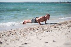 Homme dans la formation sur la plage Images stock