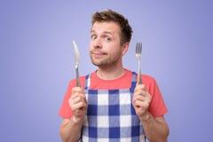 Homme dans la fourchette et le couteau de couverts de participation de tablier photo libre de droits