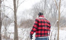 Homme dans la marche rouge par la neige Photographie stock