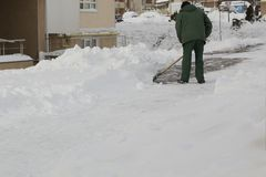 Homme dans la neige de nettoyage uniforme avec une pelle photos libres de droits