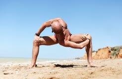 Homme dans la pose spinale intense de yoga de torsion Images libres de droits