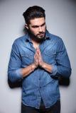 Homme dans la prière bleue de chemise Photographie stock