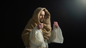 Homme dans la robe longue sortant de l'obscurité et regardant à la caméra, Messie biblique, un dieu banque de vidéos