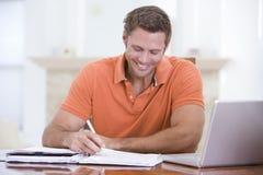 Homme dans la salle à manger avec l'écriture et le sourire d'ordinateur portatif image libre de droits