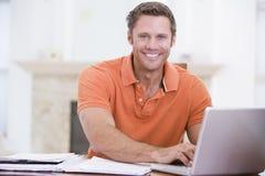 Homme dans la salle à manger avec le sourire d'ordinateur portatif Image stock