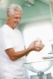 Homme dans la salle de bains appliquant la lotion après-rasage Photo stock