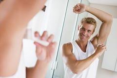 Homme dans la salle de bains appliquant le désodorisant image libre de droits