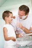 Homme dans la salle de bains mettant la crème à raser sur le jeune garçon Photos libres de droits