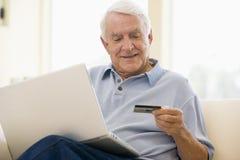 Homme dans la salle de séjour avec l'ordinateur portatif et par la carte de crédit Image stock