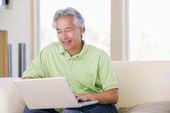 Homme dans la salle de séjour avec le sourire d'ordinateur portatif Photographie stock
