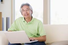 Homme dans la salle de séjour avec le sourire d'ordinateur portatif Photos stock