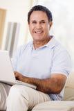 Homme dans la salle de séjour avec le sourire d'ordinateur portatif Image libre de droits