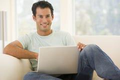 Homme dans la salle de séjour utilisant l'ordinateur portatif Photos libres de droits
