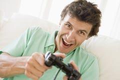 Homme dans la salle de séjour jouant des jeux vidéo Photo libre de droits