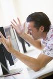 Homme dans la salle des ordinateurs frustrée au moniteur Photo stock