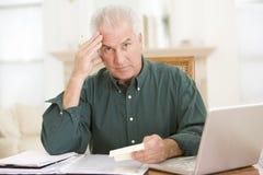 Homme dans la salle à manger avec l'ordinateur portatif et les écritures Images libres de droits
