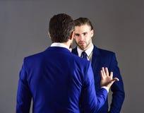 Homme dans la veste écoutant son associé avec e concentré Photographie stock