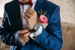 Homme dans la veste bleue avec des montres-bracelet d'usage de boutonniere Concept des bijoux, robe Images libres de droits