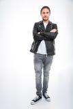 Homme dans la veste en cuir et des jeans se tenant avec des bras croisés Photo libre de droits