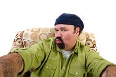 Homme dans le baiser de fauteuil et le selfie de soufflement de prise Photo stock