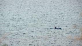 Homme dans le bateau de rangée à la mer ouverte images stock