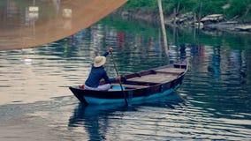 Homme dans le bateau en bois photo stock