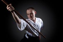 Homme dans le blanc avec l'épée en bois Photos libres de droits
