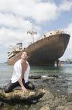 Homme dans le bord de la mer avec le bateau abandonné Photographie stock
