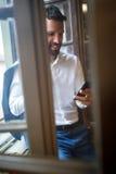 Homme dans le bureau appelle des amis au téléphone portable Photographie stock