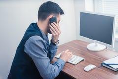 Homme dans le bureau au téléphone utilisant l'ordinateur et la dactylographie sur le clavier photos libres de droits