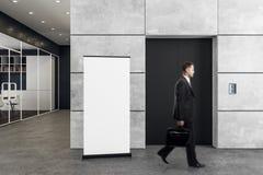 Homme dans le bureau avec l'ascenseur et l'affiche Image libre de droits